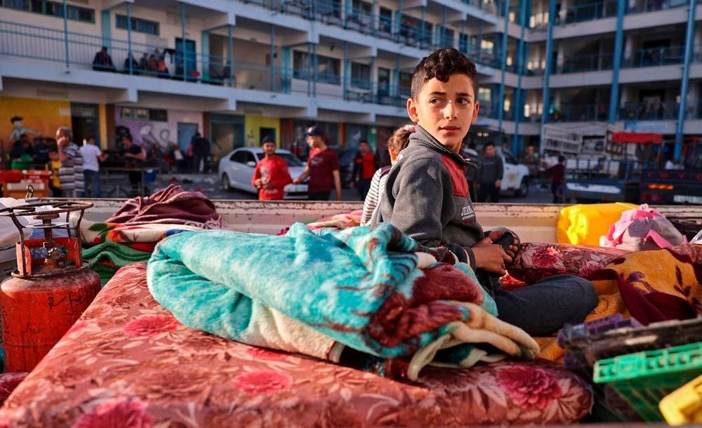 Jovem palestino obrigado a deixar sua casa em escola para abrigar refugiados, em Gaza