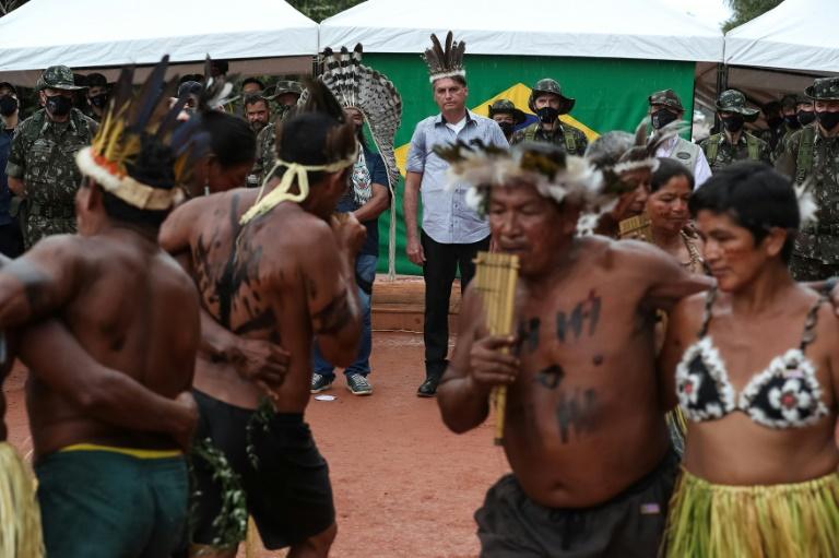 Foto da Presidência da República, divulgada em 27 de maio de 2021, mostra o presidente Jair Bolsonaro (C) assistindo a uma cerimônia indígena