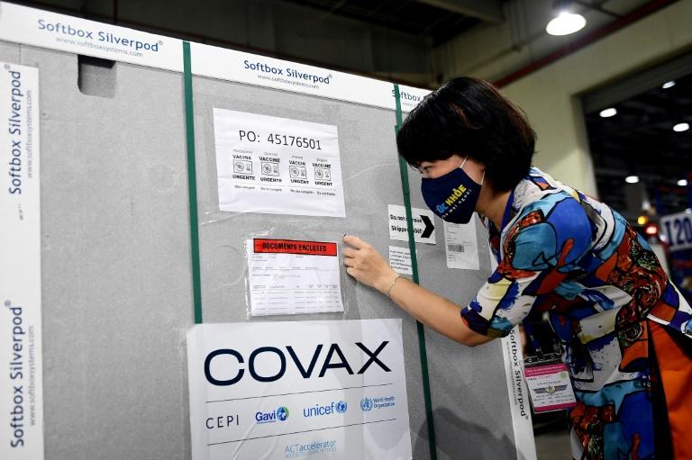 Funcionária comprova os documentos de um contêiner com o primeiro envio de doses de vacinas no aeroporto internacional de Noi Bai, Vietnã