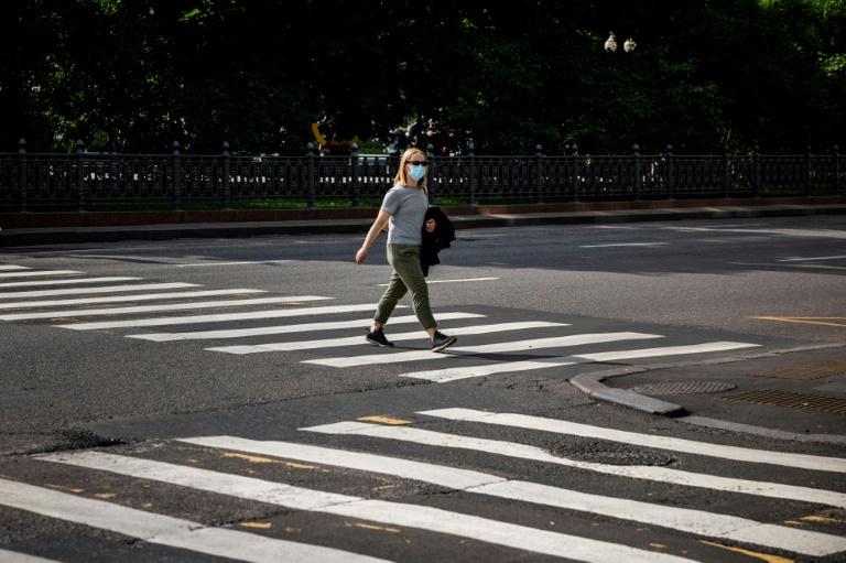 Uma mulher com máscara cruza rua em Moscou, em 12 de junho de 2021