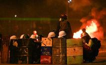 Manifestantes usando capacetes se protegem durante confrontos com a polícia em Bogotá (Juan BARRETO/Afp)