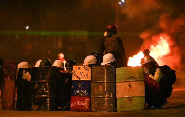 Manifestantes usando capacetes se protegem durante confrontos com a polícia em Bogotá