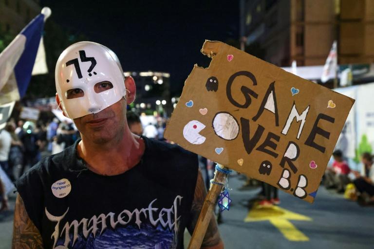 Manifestante israelense agita cartaz com o slogan