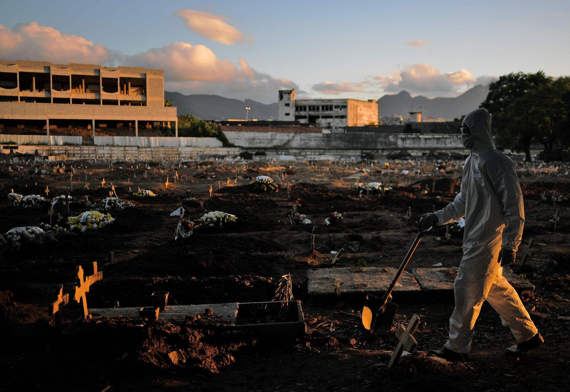 Um funcionário do cemitério de Caju, no Rio de Janeiro, anda pelas covas do local usando roupas de proteção contra a Covid