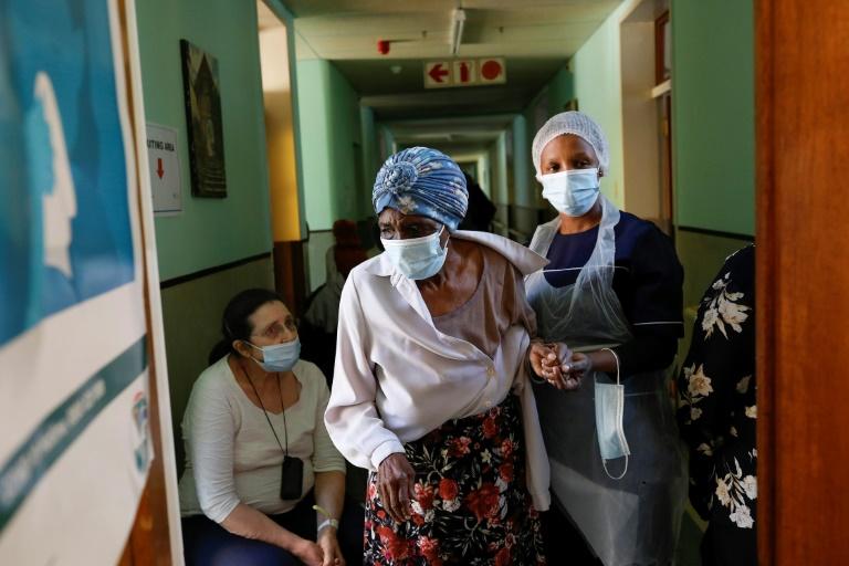 Profissional ajuda idosa antes de ser vacinada contra a Covid-19 em Petrória, África do Sul