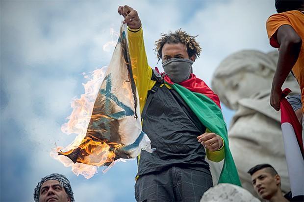 Manifestantes queimam a bandeira de Israel durante um protesto em Paris