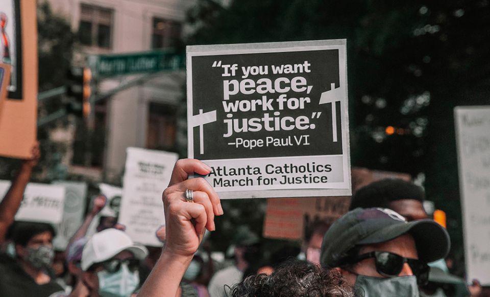 Manifestante carrega cartaz com os dizeres do papa Paulo VI 'Se você quer paz, lute por justiça'