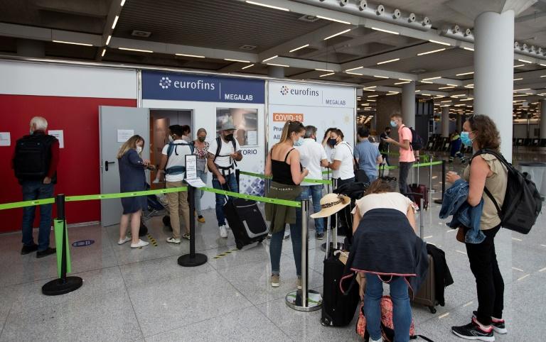 Fila de turistas em frente a um laboratório de testes de Covid-19 no aeroporto Son Sant Joan em Palma de Maiorca em 7 de junho de 2021