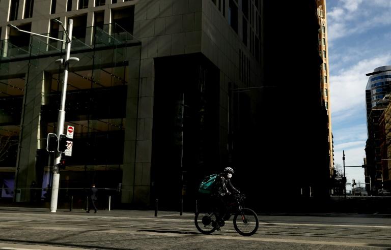 Um entregador de máscara nas ruas vazias de Sydney, Austrália, 13 de julho de 2021