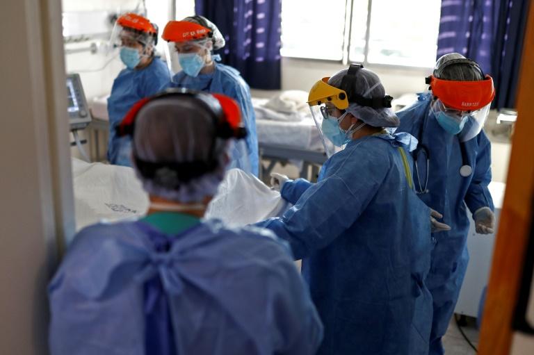 Profissionais da saúde cuidam de paciente com covid-19 na UTI do Hospital San Roque de Córdoba, Argentina