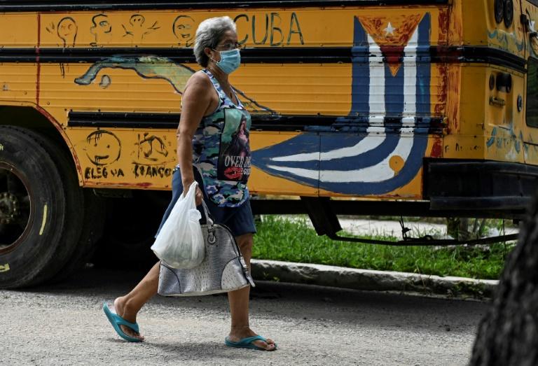Mulher caminho próximo a um ônibus com uma bandeira cubana pintada, em 19 de julho de 2021
