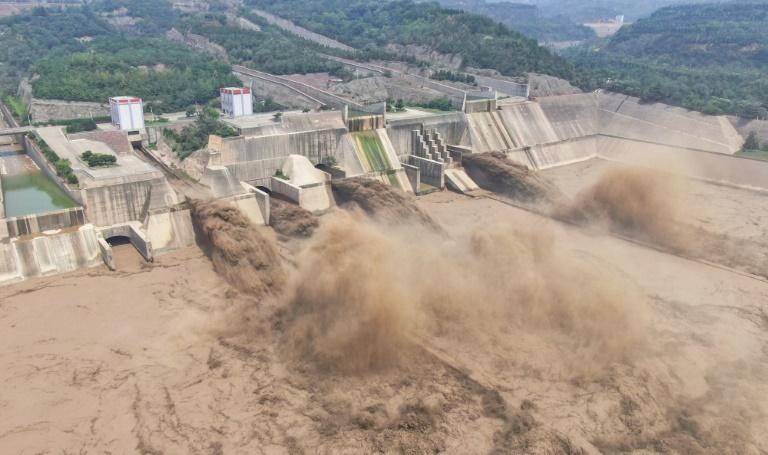 Esta foto aérea tirada em 5 de julho de 2021 mostra água sendo liberada da darragem do Reservatório Xiaolangdi em Luoyang, na província central de Henan, na China