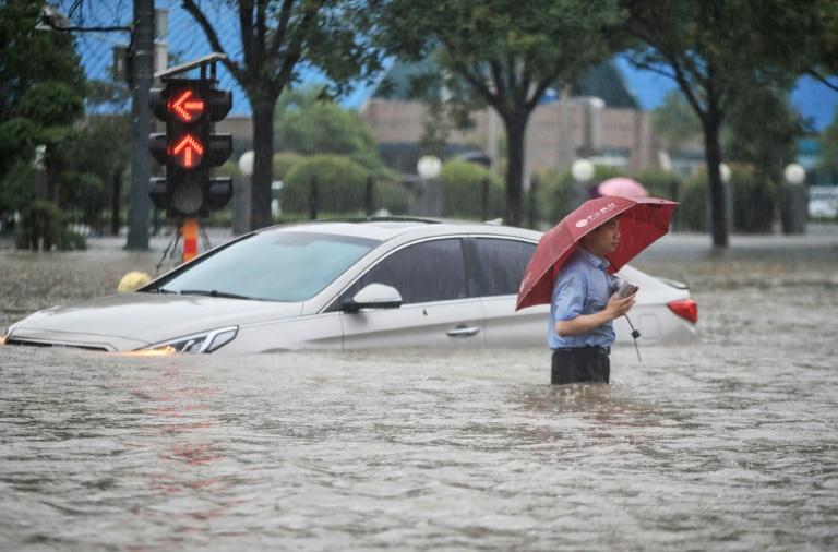 Um homem passa por um carro submerso em uma rua inundada em Zhengzhou, na China