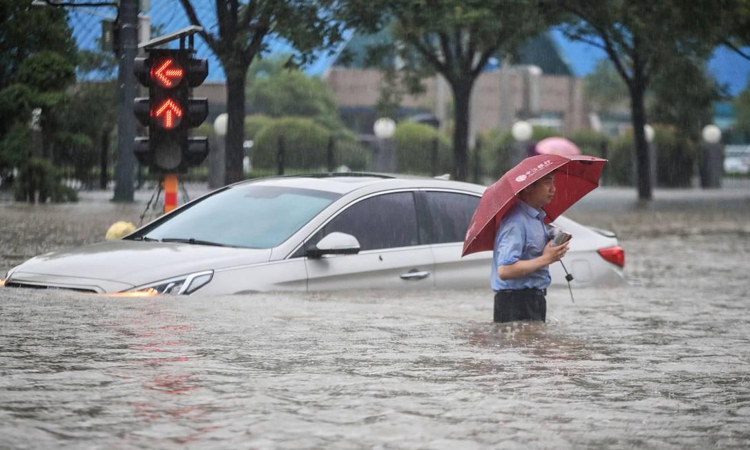 Homem passa por um carro submerso ao longo de uma rua inundada após fortes chuvas em Zhengzhou, na província central de Henan, na China