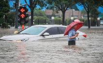 Homem passa por um carro submerso ao longo de uma rua inundada após fortes chuvas em Zhengzhou, na província central de Henan, na China (STR/AFP)