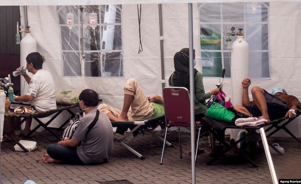 Pacientes recebem cuidados sob uma tenda, erguida num hospital para lidar com o fluxo de doentes, em Yogyakarta, Indonésia