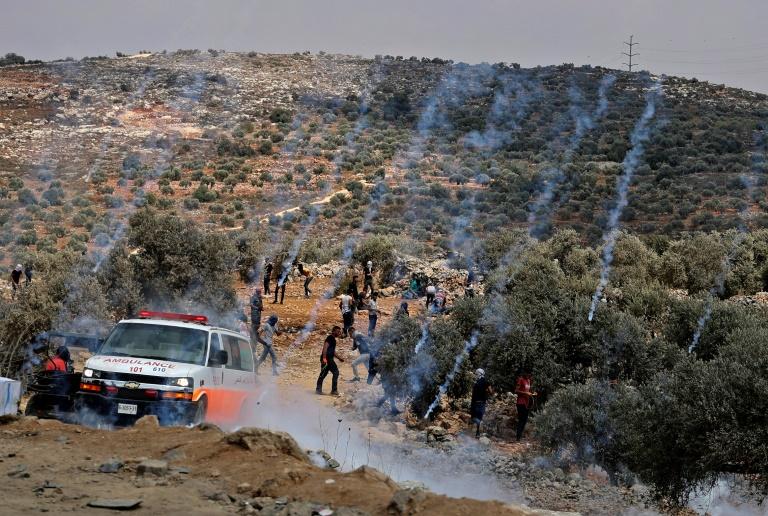 Latas de gás lacrimogêneo do exército israelense caem sobre os manifestantes palestinos em Beita, na Cisjordânia ocupada