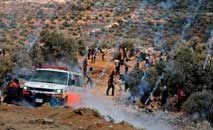 Latas de gás lacrimogêneo do exército israelense caem sobre os manifestantes palestinos em Beita, na Cisjordânia ocupada (Jaafar Ashtiyeh/AFP)