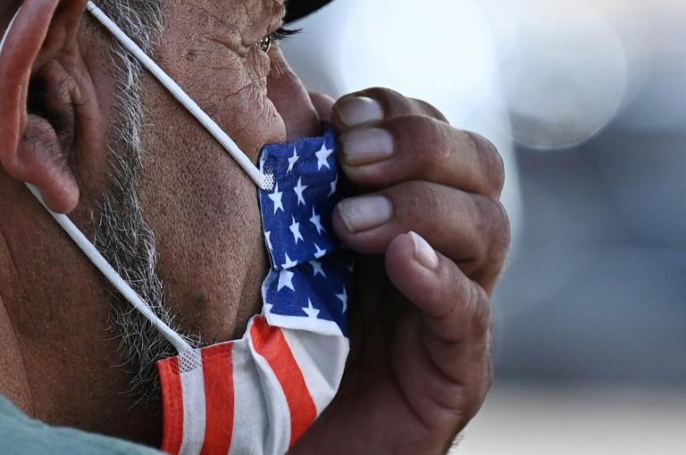 Homem ajusta máscara com a bandeira americana na Califórnia