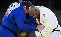 O brasileiro Rafael Silva (de azul) e o francês Teddy Riner na repescagem dda categoria até 100kg dos Jogos de Tóquio (Franck FIFE/AFP)