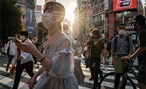 Moradores de Tóquio de máscara em um momento de aumento de casos de covid-19 (Yasuyoshi CHIBA/AFP)