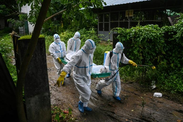 Voluntários carregam o corpo de uma vítima de covid-19 para um cemitério em Yangon, Mianmar