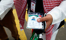 Membro da equipe saudita verifica os cartões do hajj dos peregrinos, permitindo o acesso sem contato a locais religiosos, acomodação e transporte (Fayez Nureldine/AFP)