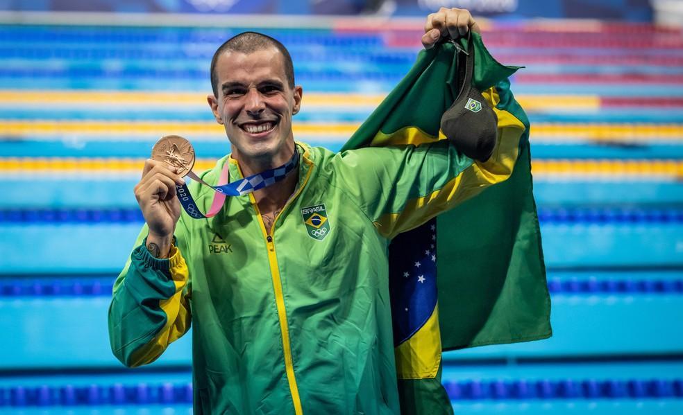 Bruno Fratus com a medalha de bronze dos 50m livre da natação nas Olimpíadas de Tóquio e a bandeira do Brasil