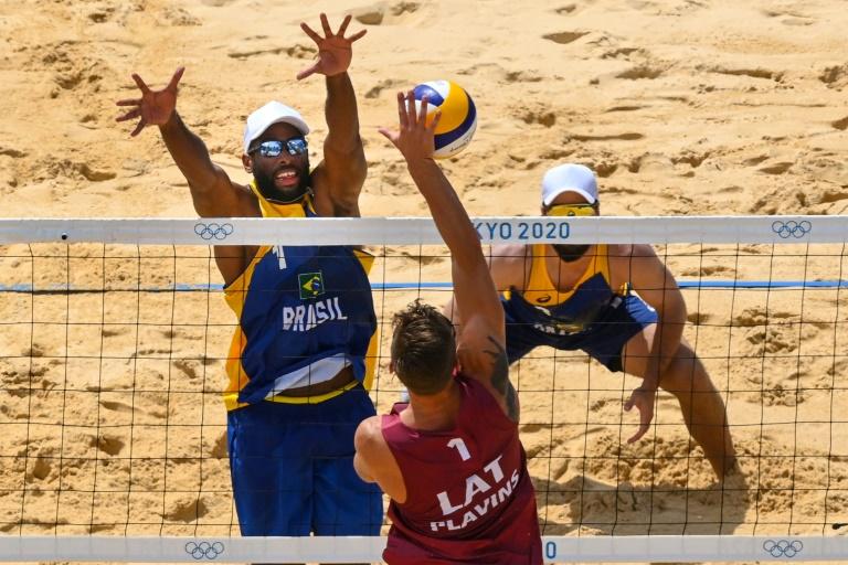 O brasileiro Evandro sobe para bloquear o ataque de Plavins, da Letônia, na partida válida pelas oitavas de final do torneio de vôlei de praia dos Jogos de Tóquio
