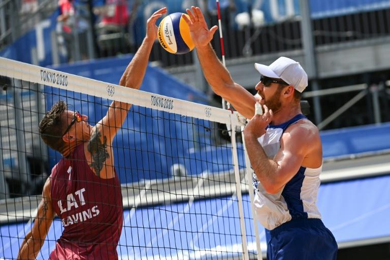 O letão Plavins (E) e o brasileiro Alison disputam uma bola nas quartas de final do vôlei de praia dos Jogos de Tóquio