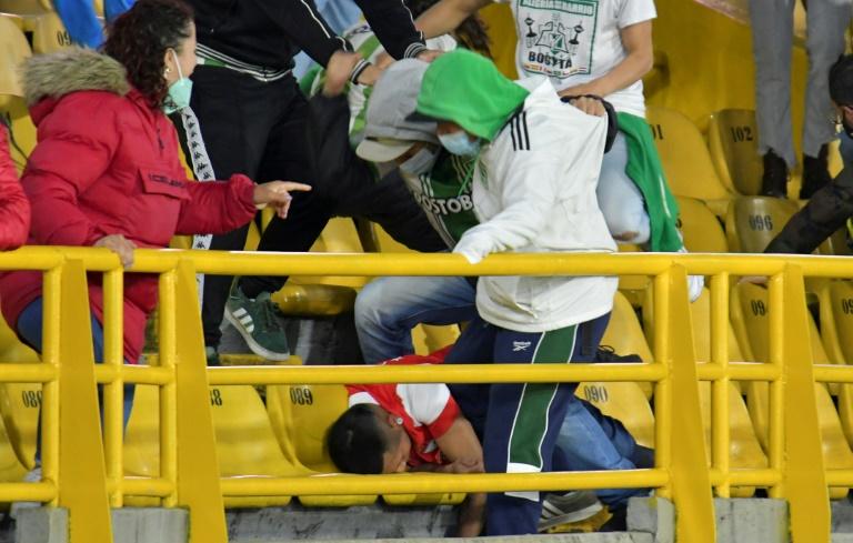Torcedores do Atlético Nacional chutam um torcedor do Independiente, Santa Fe