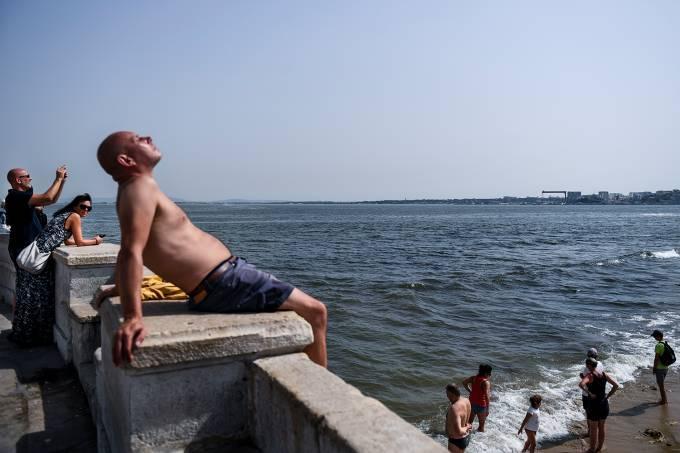 Pessoas se refrescam nas margens do rio Tagus em Lisboa, Portugal
