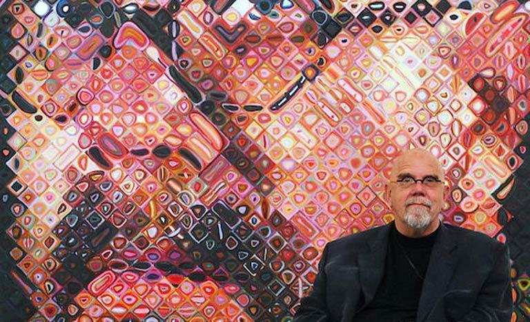 Chuck Close posa ao lado de um de seus autorretratos em seu estúdio nos EUA
