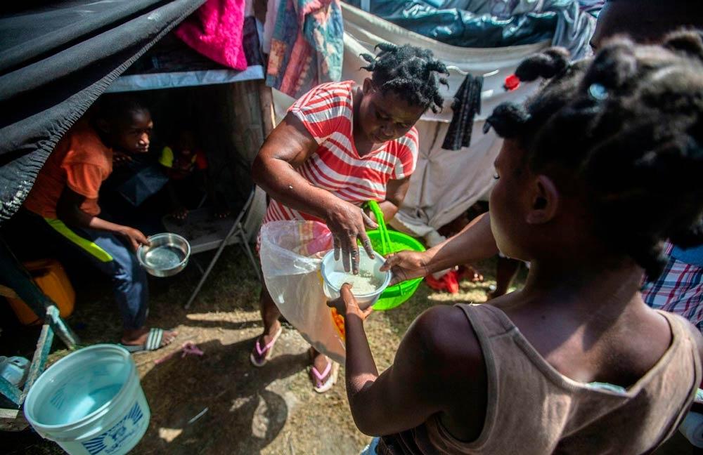 Desabrigados compartilham comida em acampamento de Les Cayes, área mais atingida pelo terremoto