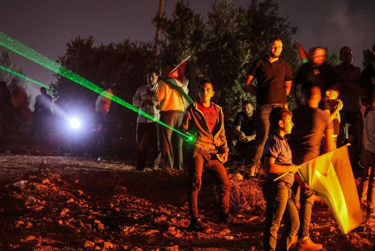 Manifestantes palestinos usam laser contra colonos israelenses no assentamento de Eviatar, na cidade de Beita, Cisjordânia