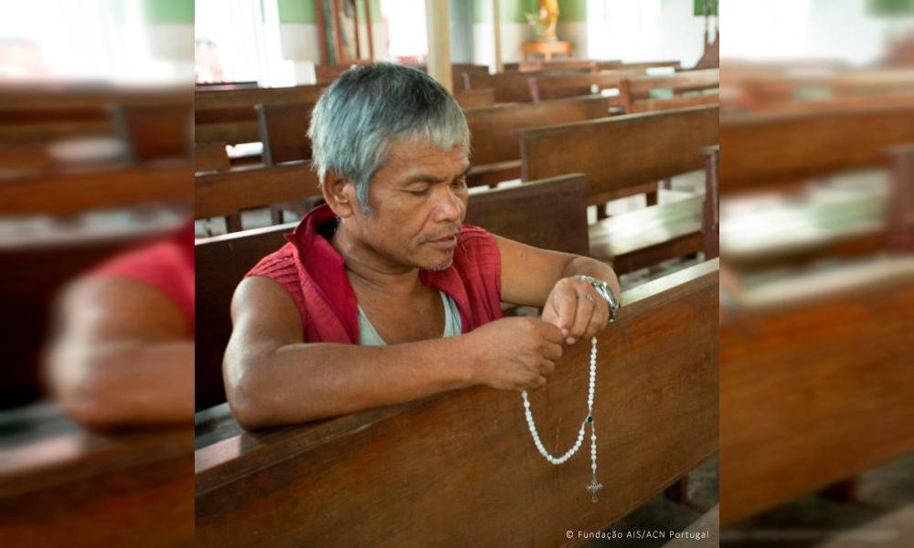 Homem reza em igreja no Mianmar