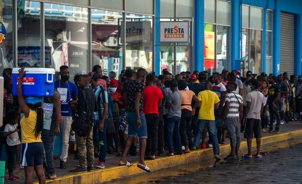 Migrantes haitianos e centro-americanos aguarda para sacar dinheiro enviado por parentes, em Tapachulas, Mèxico