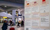 Painel em diferentes línguas mostra exigências para entrada de estrangeiros no aeroporto de Berlim (Andreas Gora/dpa/AFP)