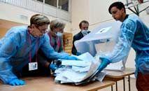 Funcionários eleitorais reúnem votos para contagem em centro de apuração (AFP)
