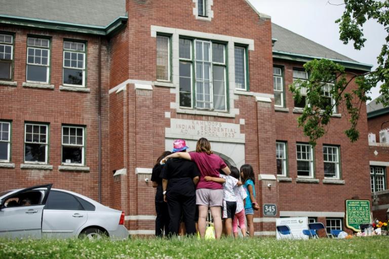 Pessoas observam o prédio do antigo internato para crianças indígenas Kamloops, onde flores e cartões foram deixados em junho de 2021 em memória das crianças cujos corpos foram encontrados enterrados no terreno da propriedade