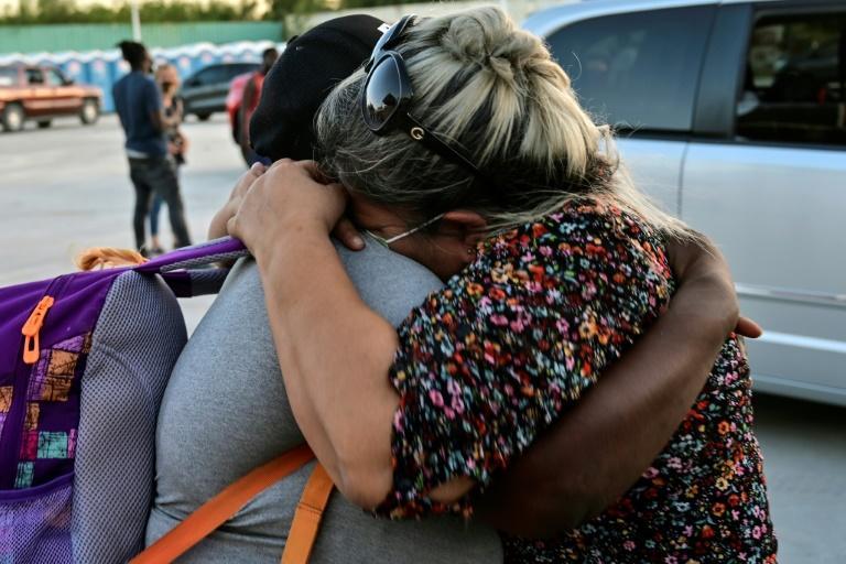 Migrantes haitianos se abraçam na chegada ao abrigo, após levantarem o acampamento na fronteira