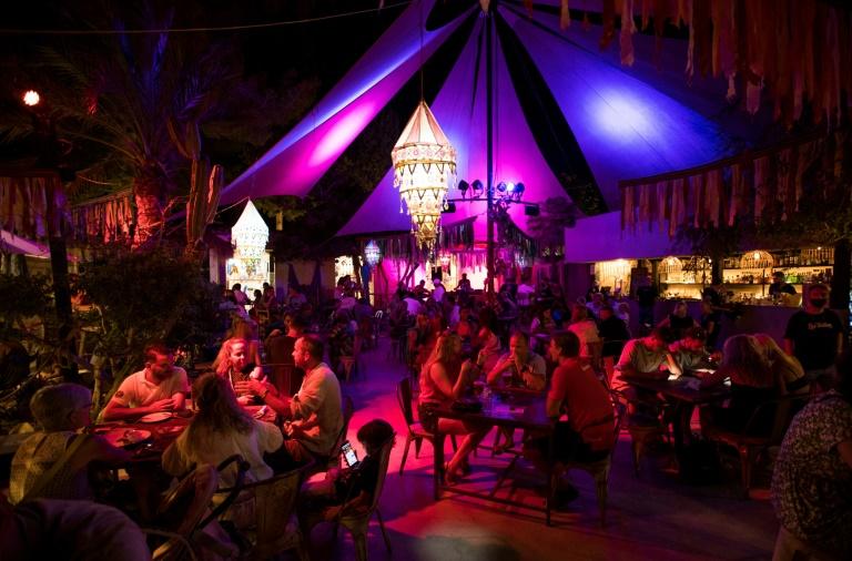 As pessoas comem e bebem no mercado noturno de Las Dalias em San Carlos, na Ilha de Ibiza, em 24 de agosto de 2021