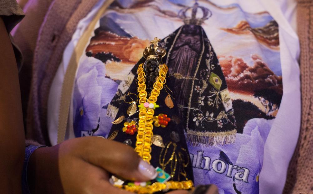 Mulher segura imagem de Nossa Senhora Aparecida durante missa no Santuário