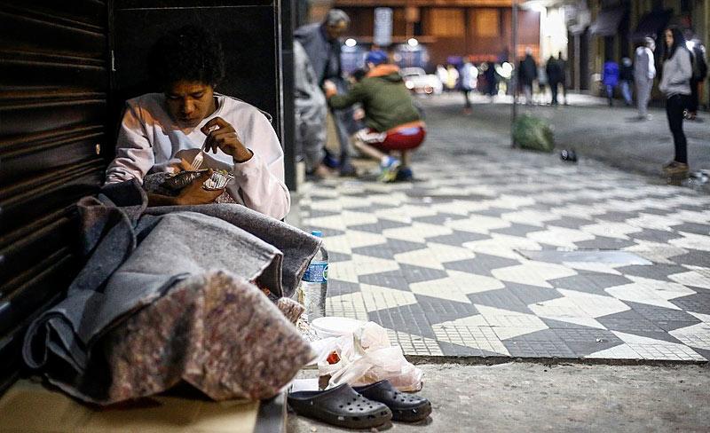 Moradora de rua em São Paulo come marmita doada por programa de voluntários