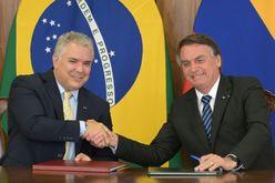 O presidente da Colômbia, Ivan Duque (E) e seu homólogo brasileiro Jair Bolsonaro se cumprimentam durante a assinatura de acordos no Palácio do Planalto, em Brasília, em 19 de outubro de 2021 (EVARISTO SA/AFP)