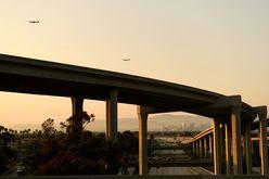 Dois aviões se aproximam do aeroporto internacional de Los Angeles para aterrissar, enquanto veículos circulam pela rodovia 110, em 16 de julho de 2021 (Patrick T. Fallon/AFP)