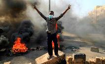 Manifestantes sudaneses queimam pneus em avenida da capital Cartum para denunciar as detenções de autoridades civis pelas Forças Armadas (AFP)