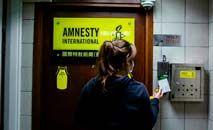 Funcionária da Anistia Internacional entra em um dos escritório, em Hong Kong (Isaac Lawrence/AFP)