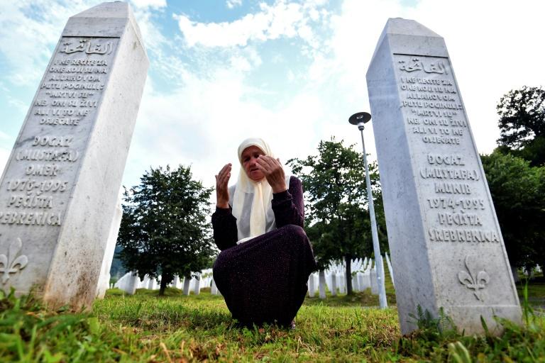 Mejra Djogaz, 71 anos, sobrevivente do massacre de Srebrenica, junto ao túmulo de seus filhos Omer, 19, e Munib, 21 (Elvis Barukcic/AFP)
