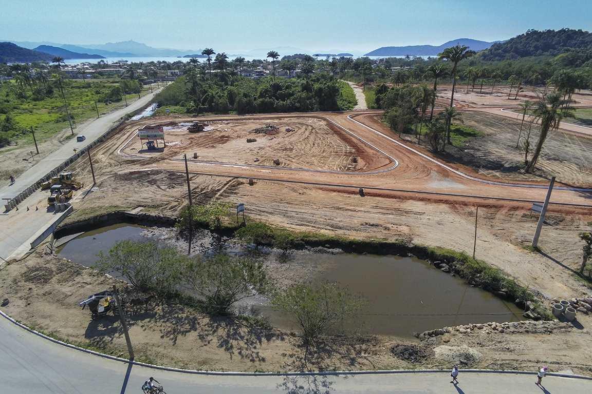 Na parte inferior da foto é possível ver um afluente do rio Jabaquara já parcialmente soterrado. Ao fundo, percebe-se a densidade do manguezal que existia no local onde o empreendimento está sendo construído (Divulgação)